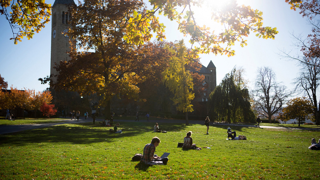 Students relax on Libe Slope in fall.