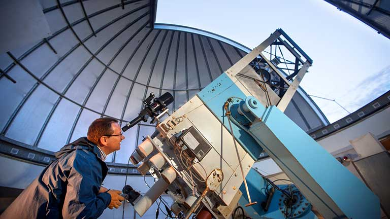 A man peers through a telescope at Fuertes Observatory