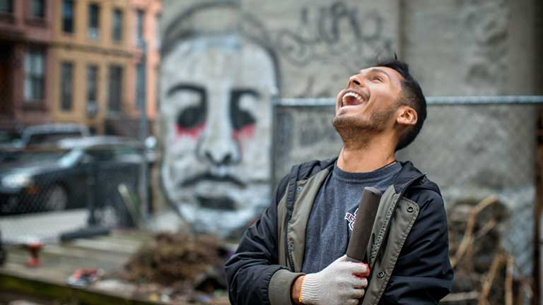 A man laughs in an urban area with graffiti in the background