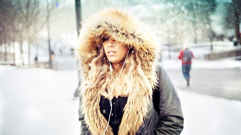 A woman walks in snow with a fur hood