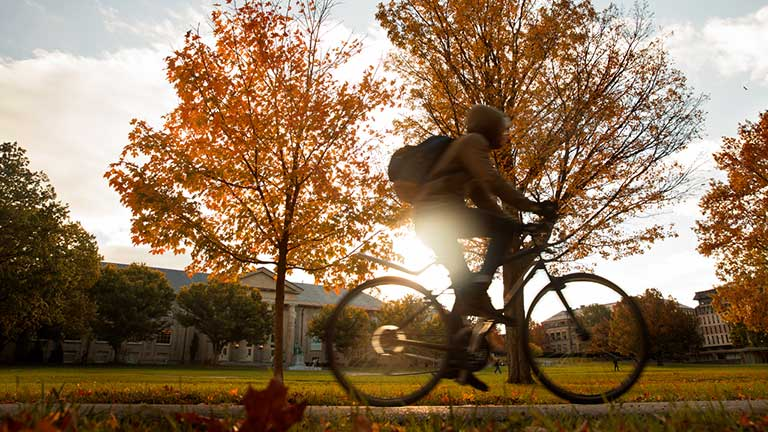 A student riding a bicycle across the Arts Quad in front of fall foliage