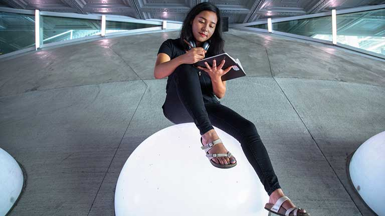A student sitting atop a glowing sphere at Milstein Hall