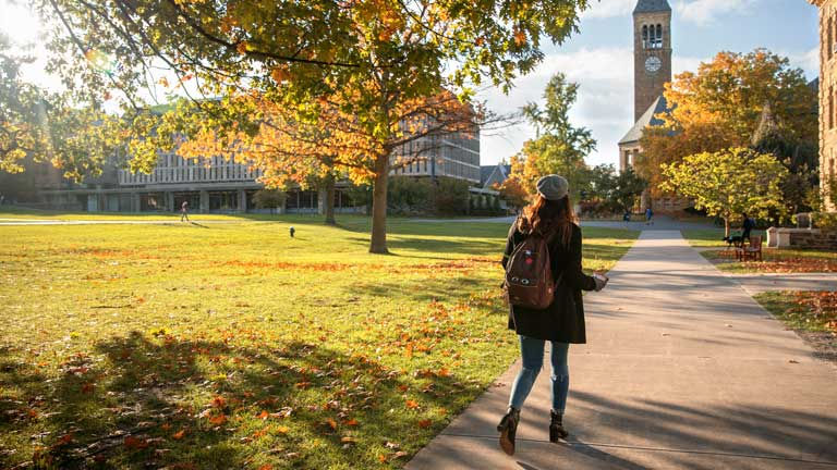 A female student wearing a hat and backpack walks towards McGraw Tower on a sunny autumn day